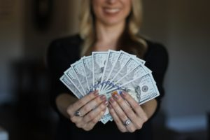 Woman holding money. Image by Sally Jermain from Pixabay